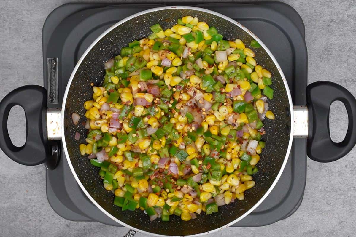 Red pepper flakes sprinkled over ready corn chaat with Italian flavors.