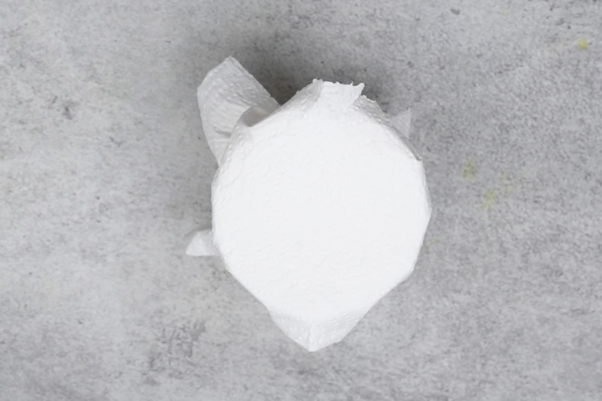 Mouth of the jar covered with a paper towel.
