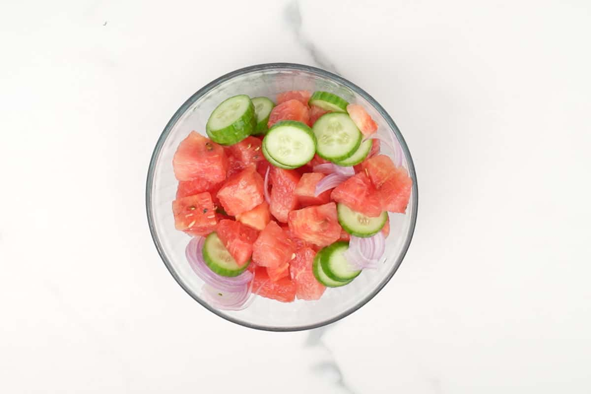 Watermelon, cucumber and onion mixd in a bowl.