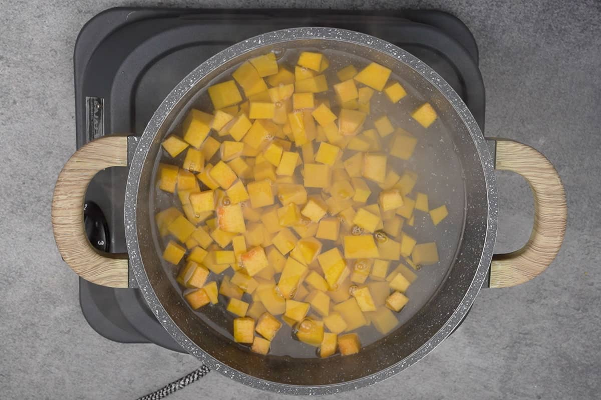 Pumpkin cubes cooking in water.