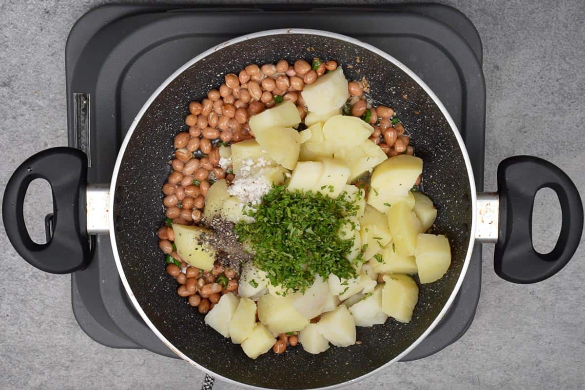 Potatoes, salt, black pepper and cilantro added to the pan.
