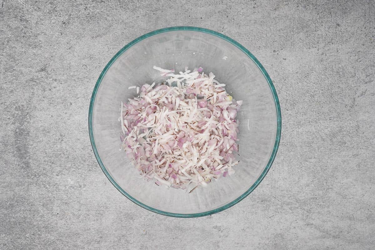 Onions, coconut, salt, sugar and lime juice mixed in a bowl.