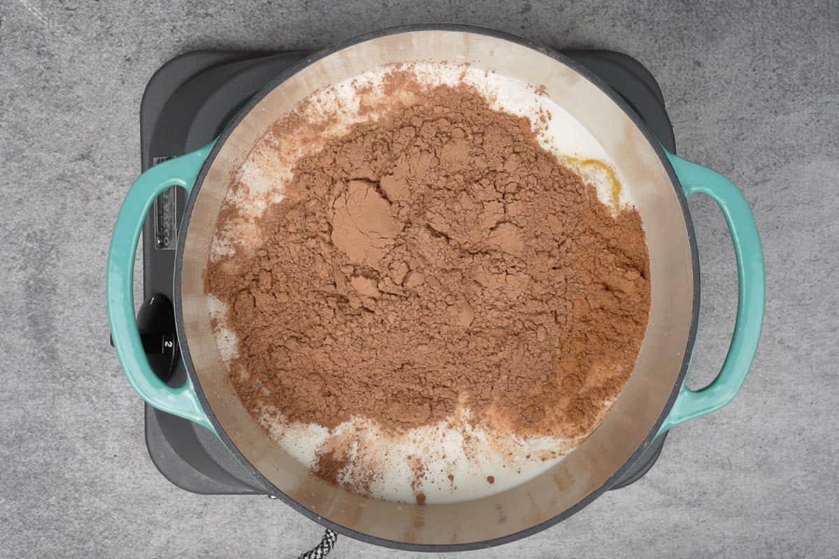 Milk, pumpkin puree, pumpkin pie spice, water, sugar and cocoa powder added to a pan.