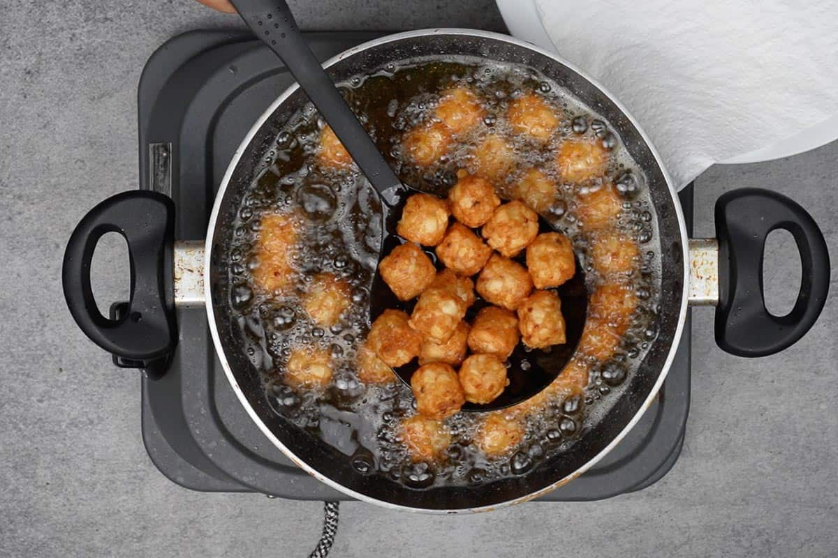 Tater tots frying in hot oil.