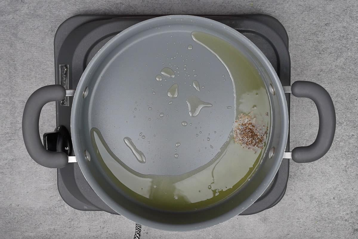Cumin seeds added to the pan.
