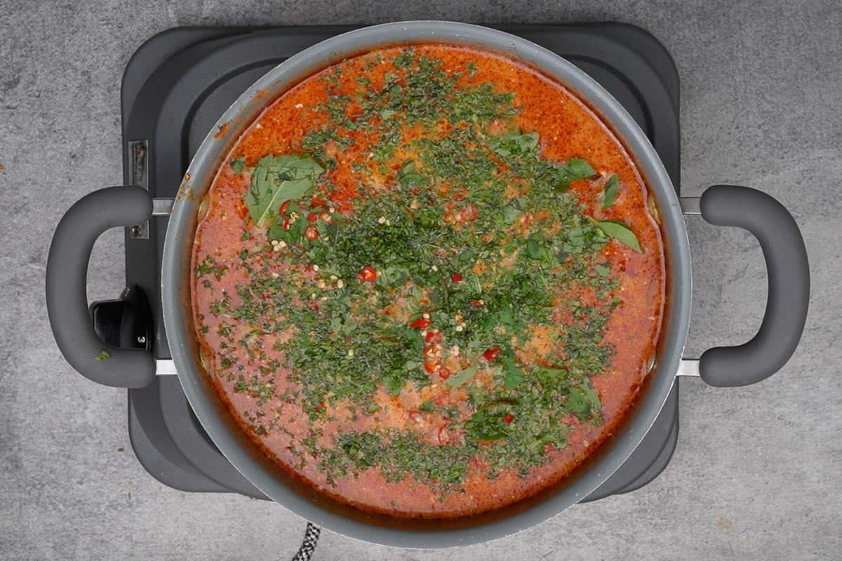 Ready Thai sweet potato curry garnished with Thai basil, cilantro and red chilies.